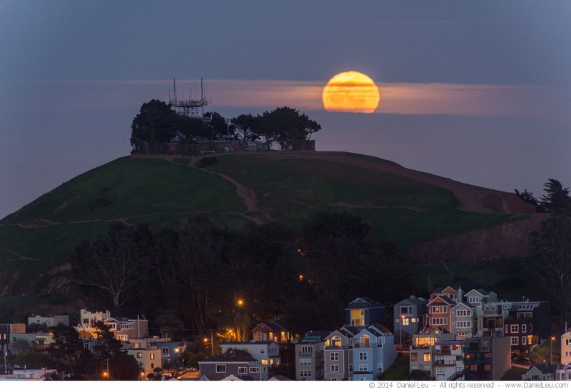 The rising full moon covered by some clouds behind the Bernal Heights Park peak.