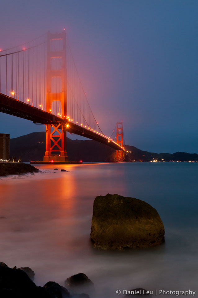 Golden Gate Bridge at sunset with fog moving slowly into the bay area.