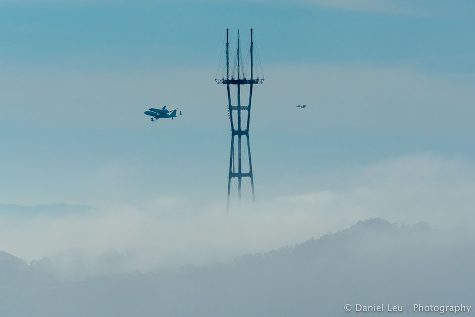 Space Shuttle Endeavour on SCA with fighter escort F-18 passing by Sutro Tower while looping over San Francisco.